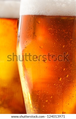 Cropped closeup of a glass of cold beer with a frothy head and water droplets from condensation beading the outside of the glass - stock photo