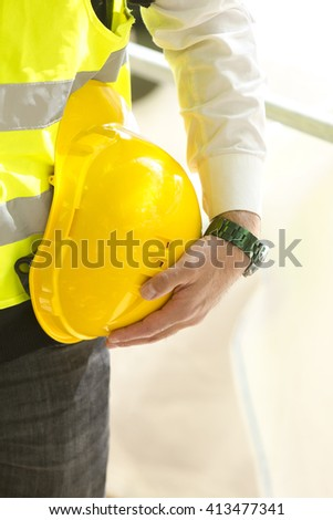 Cropped construction worker wearing safety vest holding yellow hardhat - stock photo