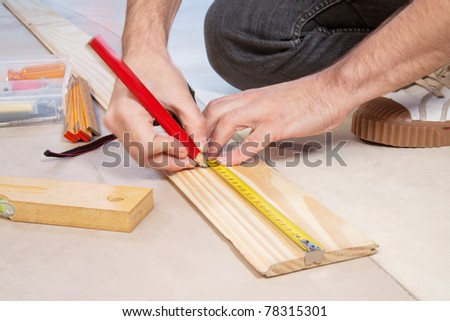 Cropped hand of a carpenter taking measurement of a wooden plank