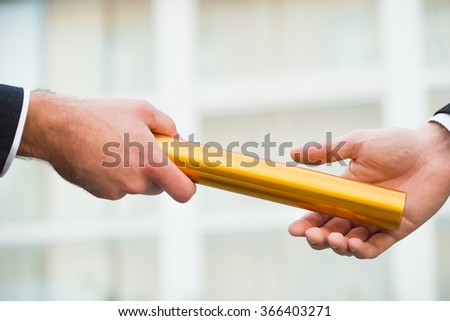 Cropped hand of businessman giving golden relay baton to colleague outdoors - stock photo