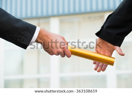 Cropped hand of businessman passing golden relay baton to colleague outdoors - stock photo