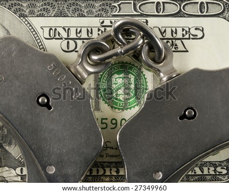 Cropped handcuffs on a one hundred dollar bill. - stock photo