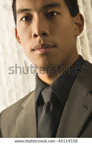 Cropped head and shoulder portrait of Asian young adult businessman. Vertical format. - stock photo