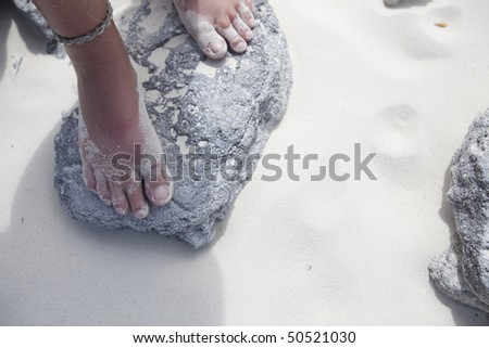 Cropped high angle view of a girl's feet standing on a rock on a sandy beach in the Caribbean. Horizontal format. - stock photo
