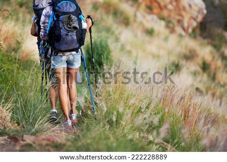 Cropped image of a backpacking couple walking along their hiking trail - stock photo