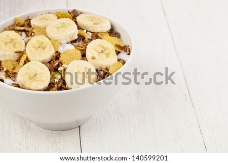 Cropped image of a bowl with cereals and a slice banana isolated on a white background