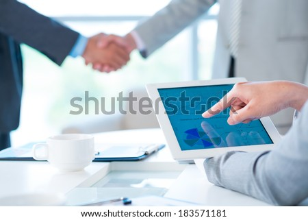 Cropped image of a business person pointing at the company activity diagram on the foreground, colleagues handshaking on the background  - stock photo