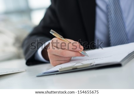 Cropped image of a businessperson signing a contract on the foreground - stock photo