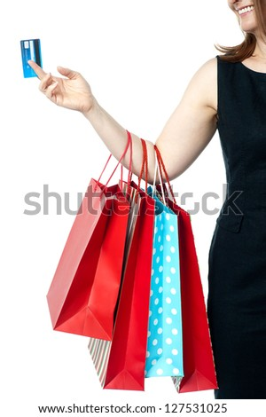Cropped image of a cheerful woman carrying shopping bags and credit card.