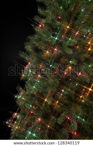 Cropped image of a Christmas tree decorated with Christmas lights against dark background. - stock photo