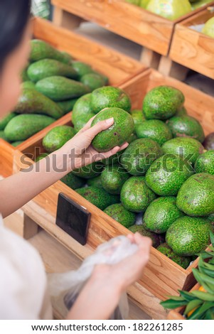 Cropped image of a customer buying ripe avocado in the grocery on the foreground  - stock photo