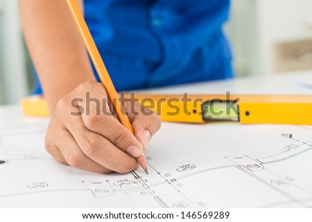 Cropped image of a draftsman correcting a blueprint - stock photo
