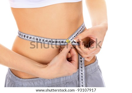 Cropped image of a fit young woman measuring her waistline - stock photo