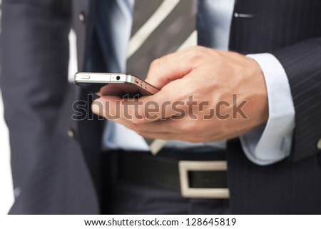 Cropped image of a human hand holding smart phone against the white surface - stock photo