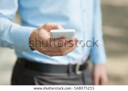 Cropped image of a male hand holding a smartphone on the foreground  - stock photo