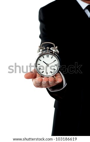 Cropped image of a man with alarm clock on his palm. Showing it to camera - stock photo
