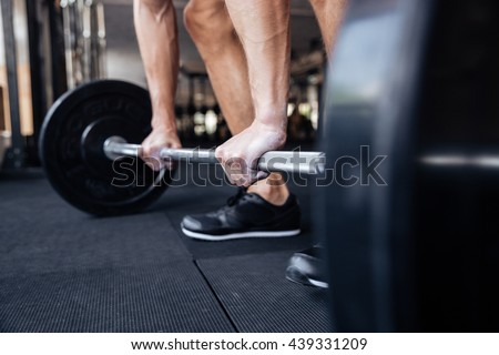 Cropped image of a muscular fitness man lifting heavy barbell at the gym - stock photo