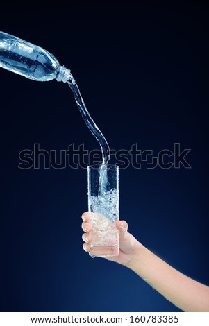 Cropped image of a person holding a glassware where water is pouring isolated on blue - stock photo
