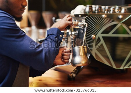 Cropped image of a professional barista steaming milk on a coffee machine with skill - stock photo