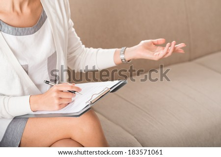 Cropped image of a psychiatrist gesturing while making notes during therapy session  - stock photo