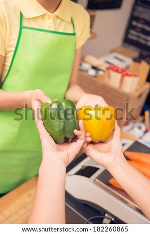 Cropped image of a saleswoman taking colorful pepper to weight on the foreground  - stock photo