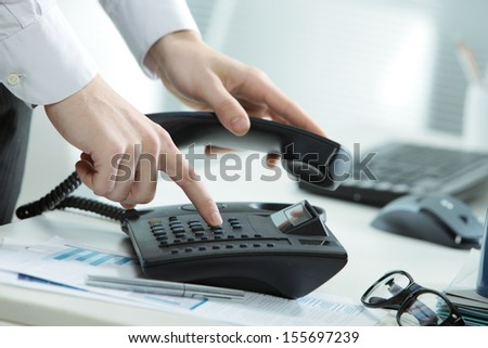 Cropped image of a telephone on a desk with a hand taking the receiver off hook - stock photo