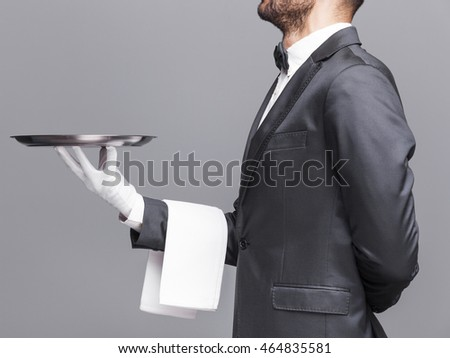 Cropped image of a waiter holding a silver tray on gray background