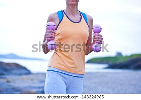 cropped image of a woman holding weights on the beach - stock photo