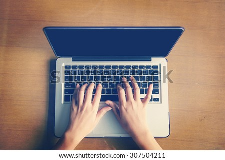 Cropped image of a woman working on  laptop top view - stock photo