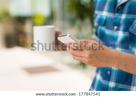 Cropped image of a young guy with a cup of coffee calling by smartphone on the foreground  - stock photo