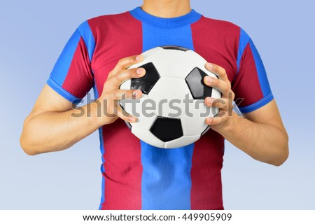 Cropped image of a young man holding a soccer ball his hands with colors red and blue in barcelona - stock photo