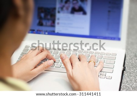 Cropped image of a young woman working on his laptop in a coffee shop, - stock photo