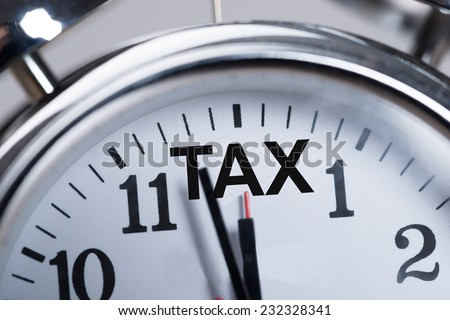 Cropped image of alarmclock showing arrival of tax time - stock photo