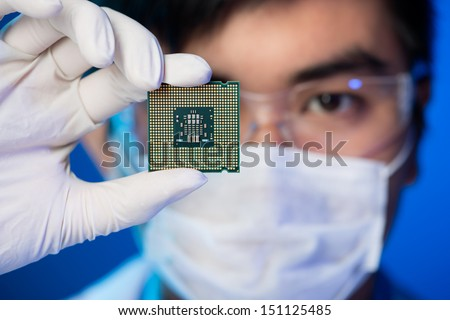 Cropped image of an engineer showing a computer microchip on the foreground - stock photo