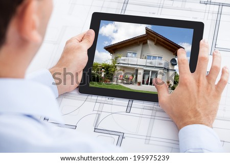 Cropped image of architect analyzing house on digital tablet over blueprint in office - stock photo