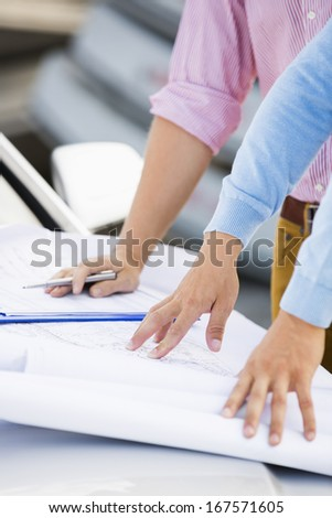 Cropped image of architects with blueprints on car at site - stock photo