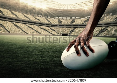 Cropped image of athlete holding rugby ball against rugby stadium - stock photo