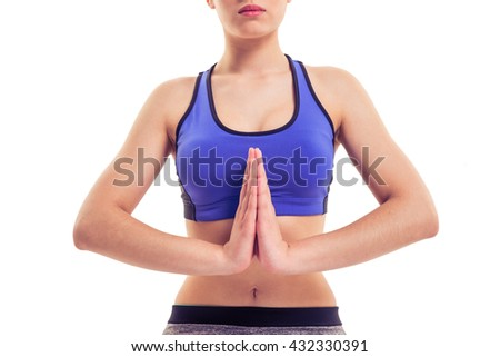 Cropped image of attractive young woman in sportswear is doing yoga, isolated on white background - stock photo
