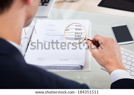 Cropped image of auditor examining invoice with magnifying glass at desk - stock photo