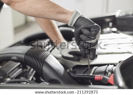 Cropped image of automobile mechanic repairing car in automobile store - stock photo