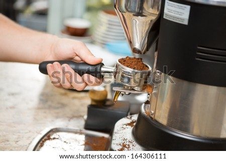 Cropped image of barista holding portafilter with ground coffee in cafe - stock photo