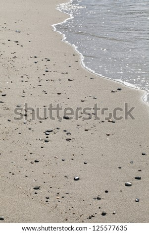 Cropped image of beach sand and water edge seen in Puerto galera Philippines