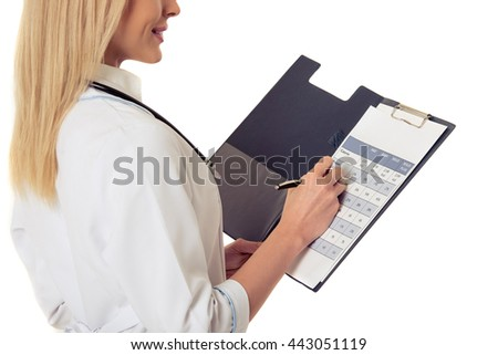 Cropped image of beautiful female doctor in white coat holding a folder, making notes and smiling, isolated on white background