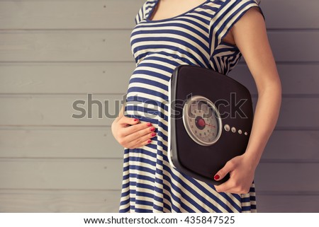 Cropped image of beautiful pregnant woman holding weigh scales and keeping one hand on a belly, standing against gray wall - stock photo