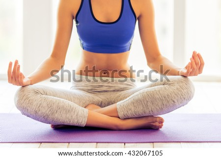 Cropped image of beautiful young woman in sportswear meditating while sitting in lotus pose on yoga mat against window