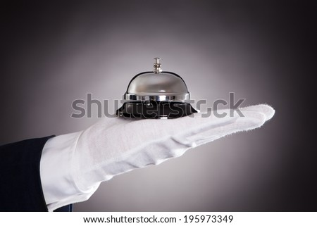 Cropped image of bellman holding bell against black background - stock photo