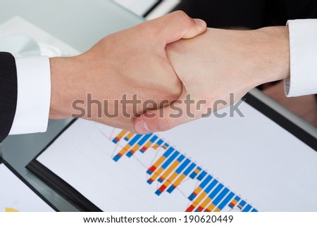 Cropped image of business colleagues shaking hands in office - stock photo