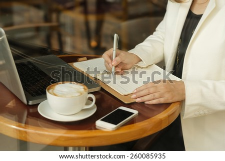 Cropped image of business lady working while sitting in the cafe - stock photo