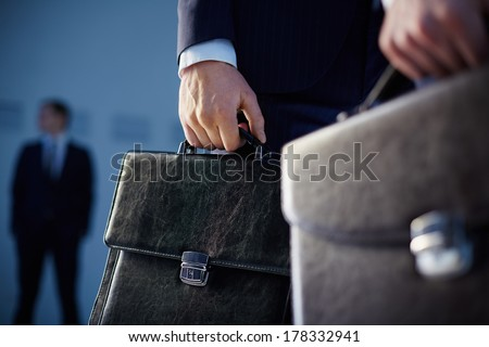 Cropped image of business partners carrying briefcases on the foreground while their colleague standing on the background  - stock photo