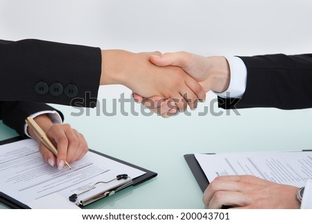 Cropped image of business people shaking hands during office meeting